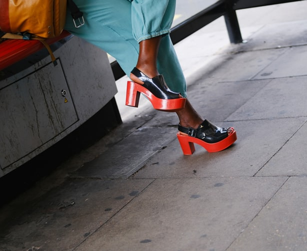 woman wearing black and red block heeled platforms with blue pants
