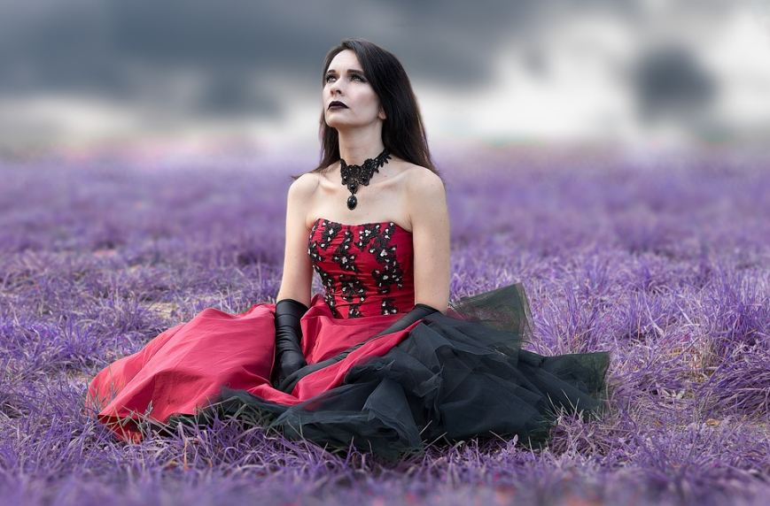 a gothic woman sitting on the grass